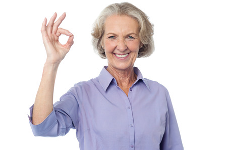ok sign: Smiling senior lady gesturing perfect sign