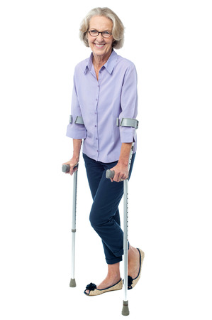 Senior courageous woman with the help of crutches photo