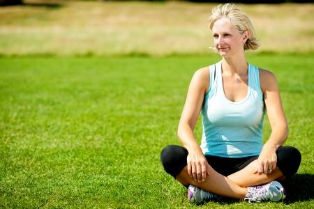 緑豊かな緑の芝生の上に座っている中年の女性