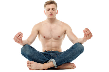 Young man gathering peace while meditating photo
