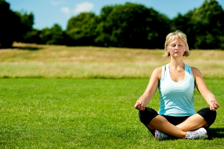 Isolated middle aged woman meditating outdoors photo