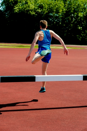Back view of male athlete after crossing hurdle photo