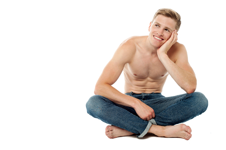 crossed legs: Young man sitting on the studio floor and thinking Stock Photo