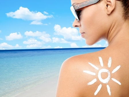 sunblock: Rear view image of a woman with sunscreen lotion