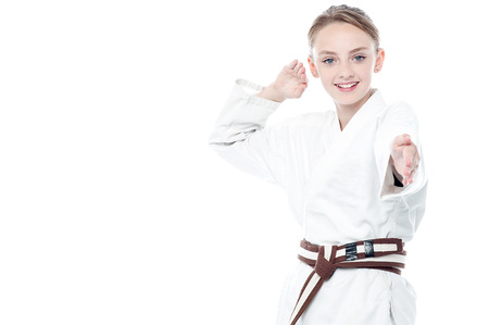Young karate fighter in action over white photo