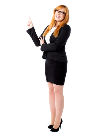 Young female executive pointing and looking upwards Stock Photo