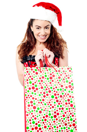 Smiling lady wearing santa cap and holding bag photo