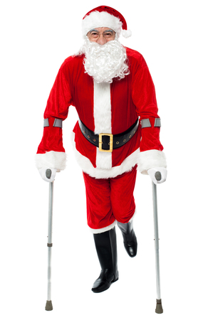Male santa claus walking with help of crutches photo
