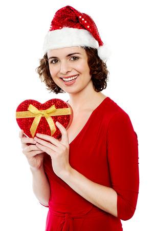Cheerful young santa woman holding xmas gift photo