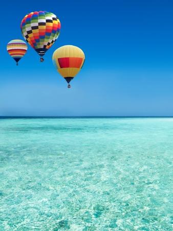 カラフルな熱気球、青い海の上を飛んで 写真素材