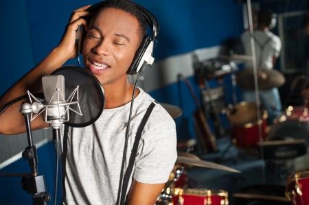 cantando: Cantante masculino joven en el estudio de grabaci�n Foto de archivo