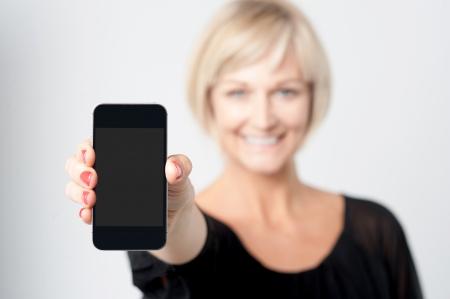 女性紹介新しい携帯電話の笑みを浮かべてください。