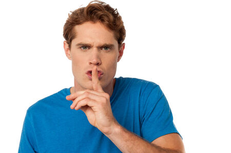 Young casual male shows silence gesture