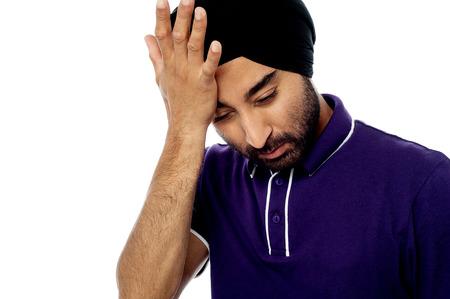 wincing: Man suffering from headache, wincing.