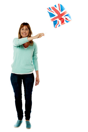 Woman waving UK flag, full length portrait. photo