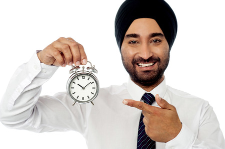 Businessman holding up alarm clock. photo
