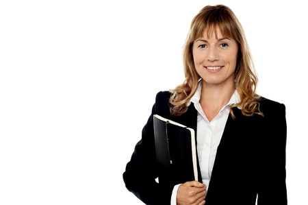 Pretty female executive holding notebook