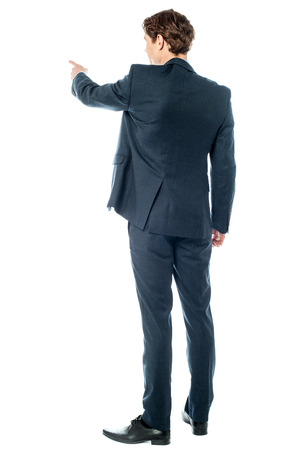 Back pose of a casual businessman pointing photo