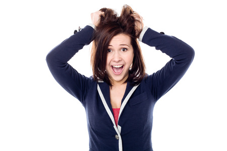 madness: Playful young female pulling her hair out in madness Stock Photo