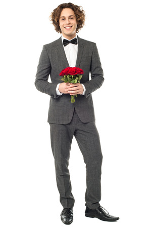 dashing: Dashing groom in a tuxedo holding a bunch of red roses