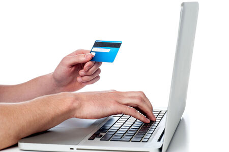 accessing: Mans hand  holding credit card and accessing his laptop Stock Photo