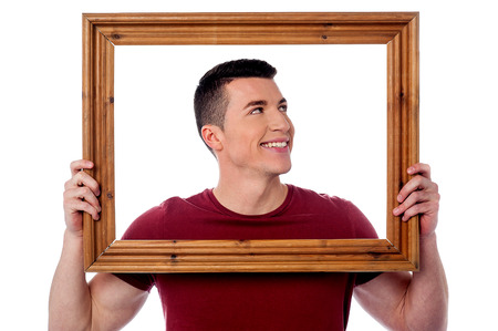 Smiling guy holding wooden picture frame and looking away photo