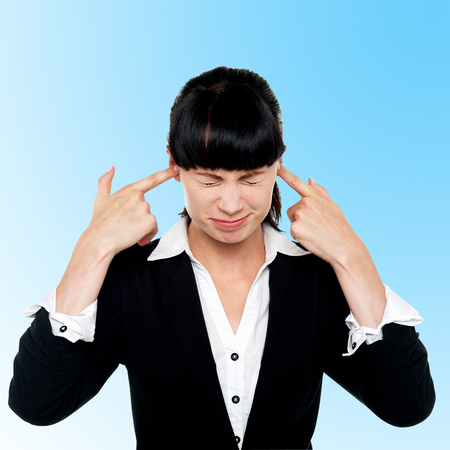 Businesswoman closing ears with her fingers photo
