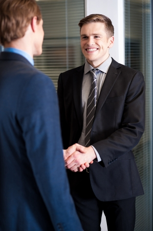formals: Handsome young businessmen shaking hands Stock Photo