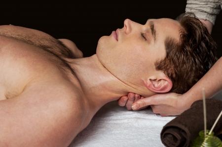 massage huile: Jeune homme recevant un massage de la tête au spa santé