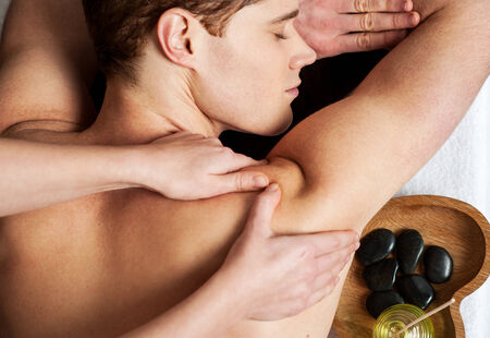 Hands of a masseur giving a back massage photo