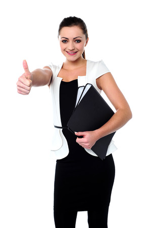 Smiling female executive showing thumbs up