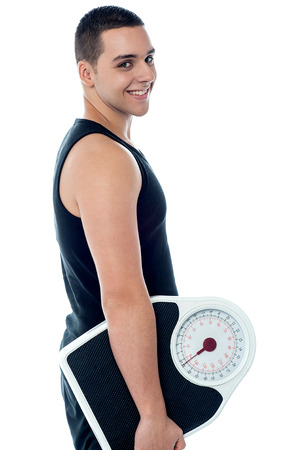 Smiling young fitness trainer holding weighing scale photo