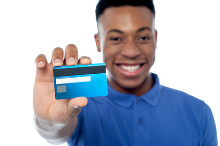Happy young guy showing credit card photo