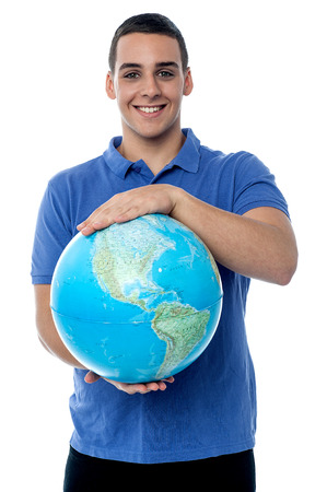 Handsome young man holding a globe on a white background photo