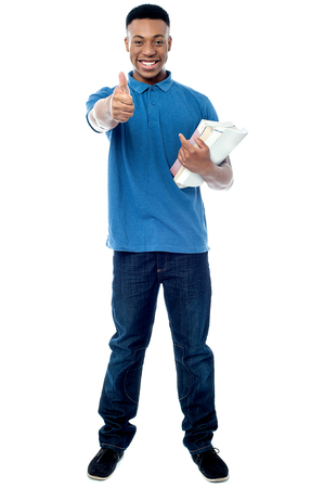 Student holding books and showing thumps up sign to camera Stock Photo