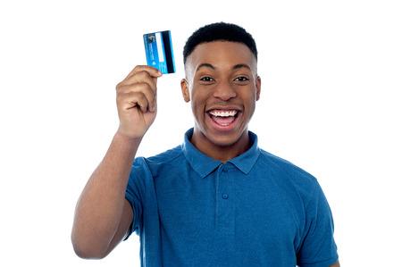 幸せな若い男が彼のクレジット カードを表示します。 写真素材