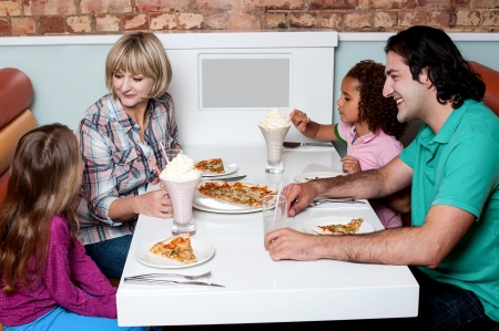 Family of four having great time in a restaurant photo