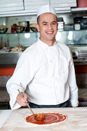 pizza base: Cheerful chef preparing the pizza base