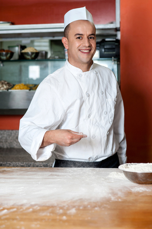 pizza base: Young male baker preparing pizza base Stock Photo