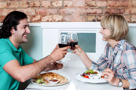 Beautiful couple toasting with wine in restaurant photo
