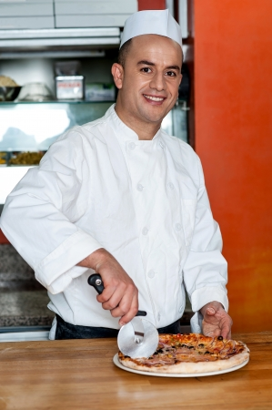 Young male chef cutting pizza before delivery photo