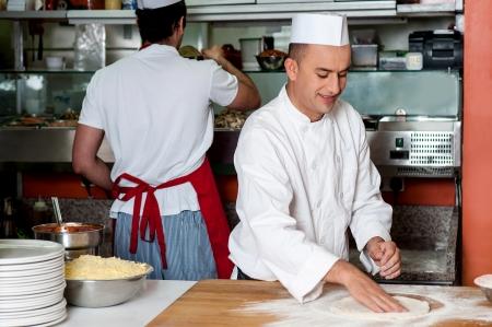 pizza base: Young male chef preparing pizza dough