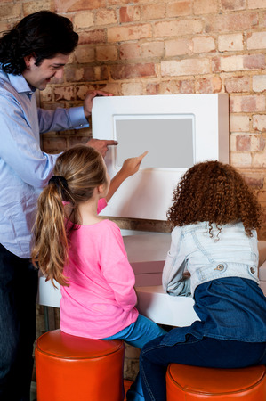 Man showing daughters how to order pizza online photo