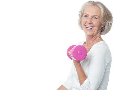 Ältere Frau im Fitness-Studio arbeitet mit Hanteln