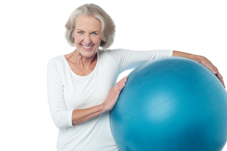 Fit aged woman holding big blue exercise ball