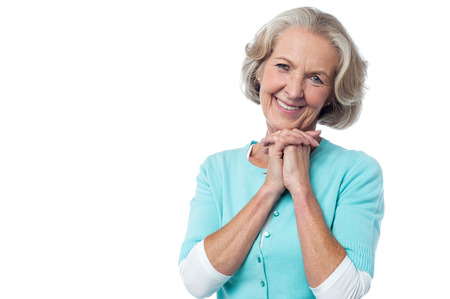 shy woman: Attractive aged lady posing with clasped hands Stock Photo