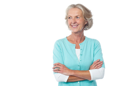Confident aged woman in casuals, arms crossed. photo