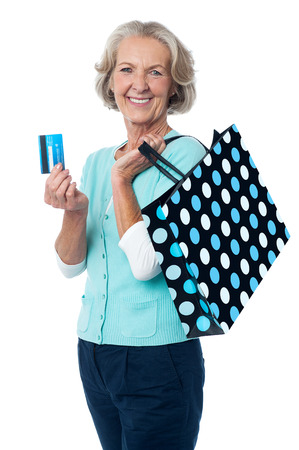 woman credit card: Senior woman posing with shopping bags and credit card Stock Photo