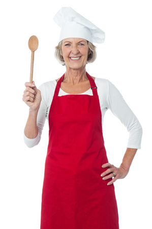wooden spoon: Joyous smiling aged female chef holding spoon Stock Photo