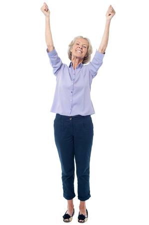 mature female: Excited senior citizen raising her hands